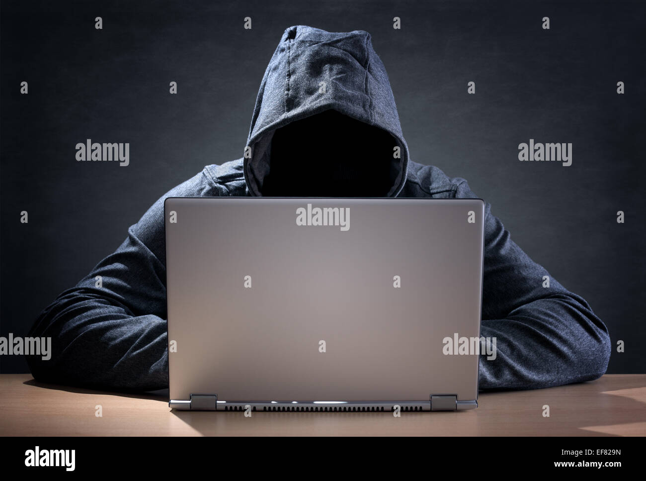 Computer hacker stealing data from a laptop - Stock Image