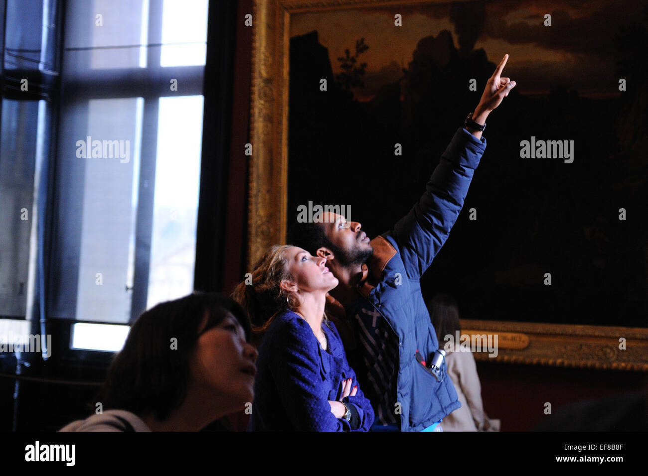 PARIS - MAR 1: Tourists look at the paintings at the Louvre Museum (Musee du Louvre) on March 1, 2014 in Par - Stock Image