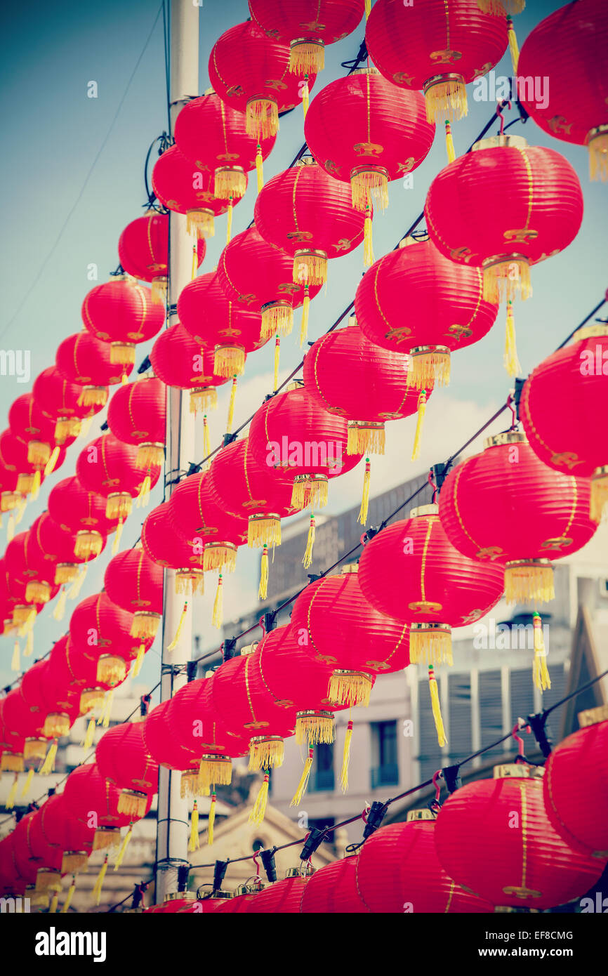 Retro filtered Chinese red paper lanterns against blue sky. - Stock Image