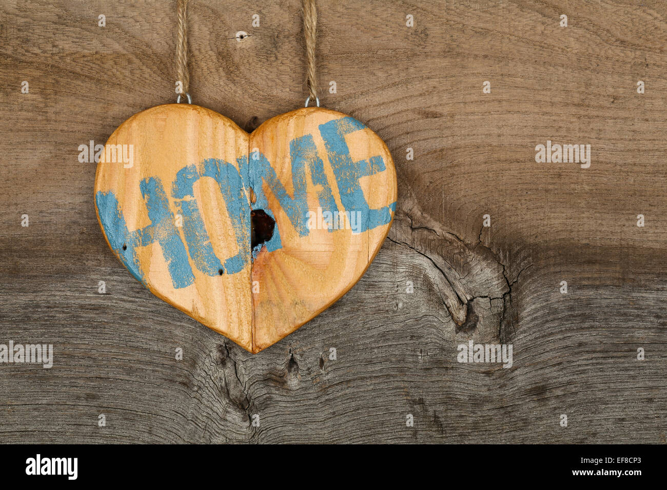 Love Home message wooden heart sign from recycled old palette on rough grey wooden background, copy space - Stock Image