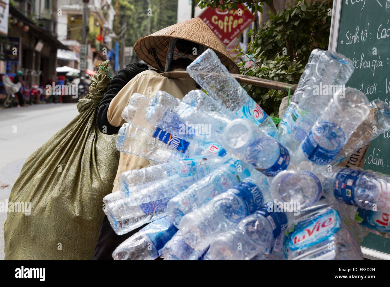 Woman carrying plastic bottles collected for recycling, Cau May street, Sapa, northern Vietnam - Stock Image