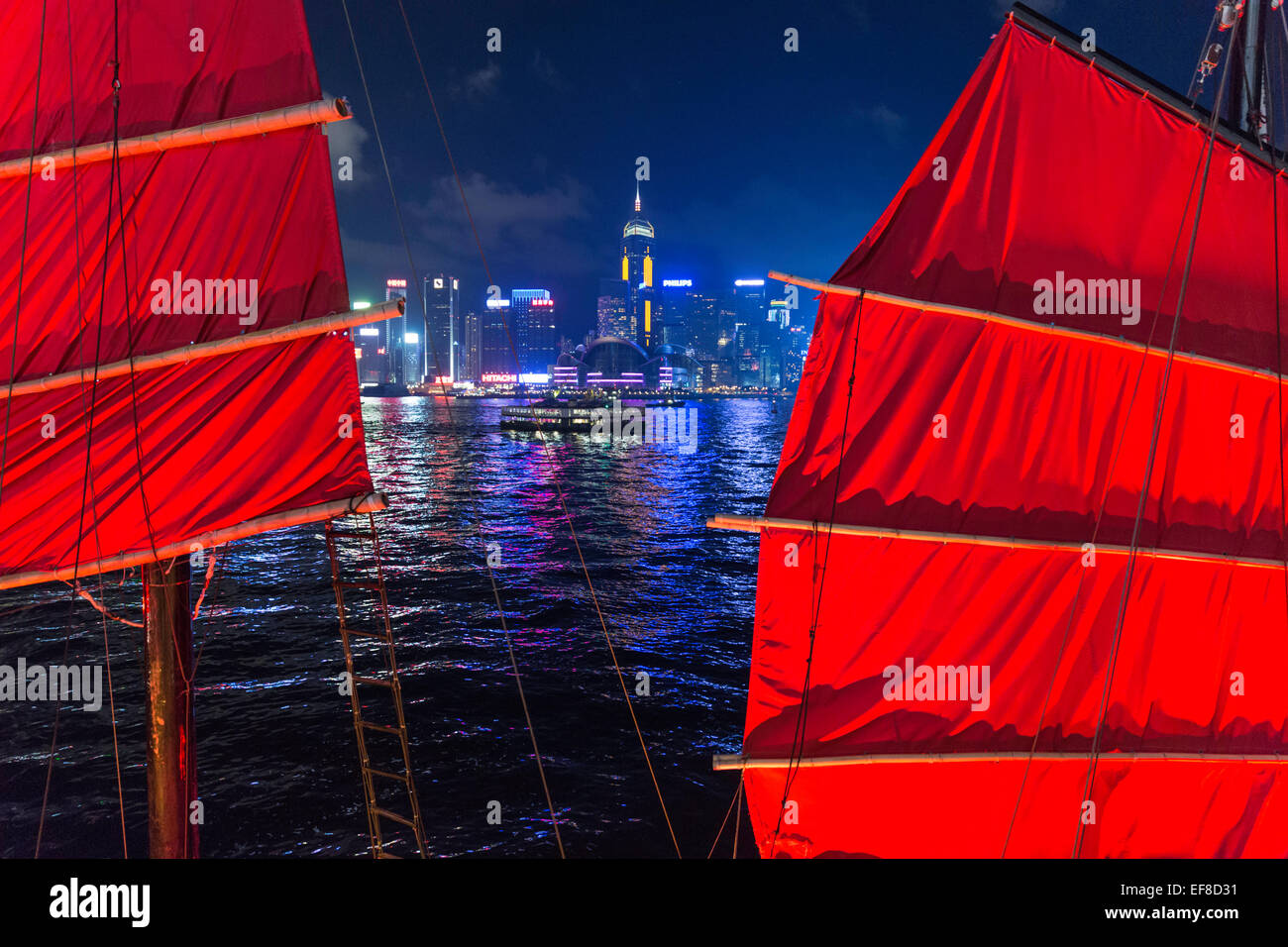 Night view of Hong Kong skyline from Kowloon side with sails of junk in foreground - Stock Image