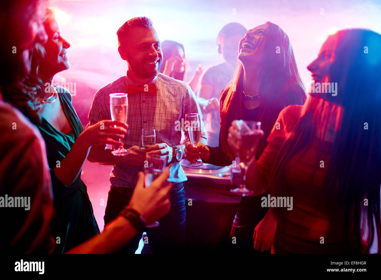 Ecstatic friends with champagne talking at party in night club - Stock Image