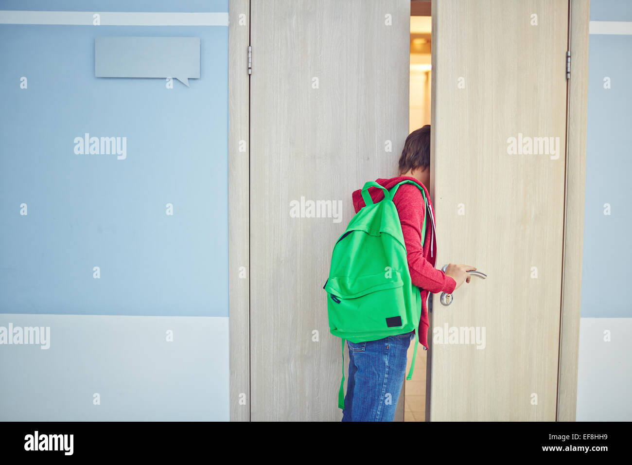 Pre-teen schoolboy late for lesson looking into classroom - Stock Image