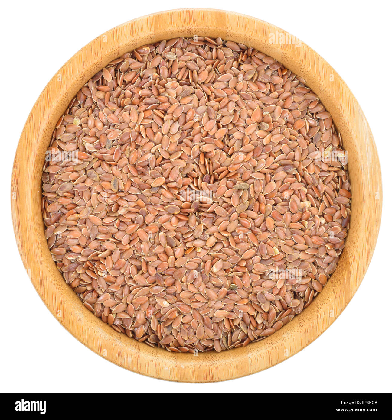 Brown flax seeds in wooden bowl isolated on white background. Flax seeds are rich in omega-3 fatty acid. Top view. - Stock Image