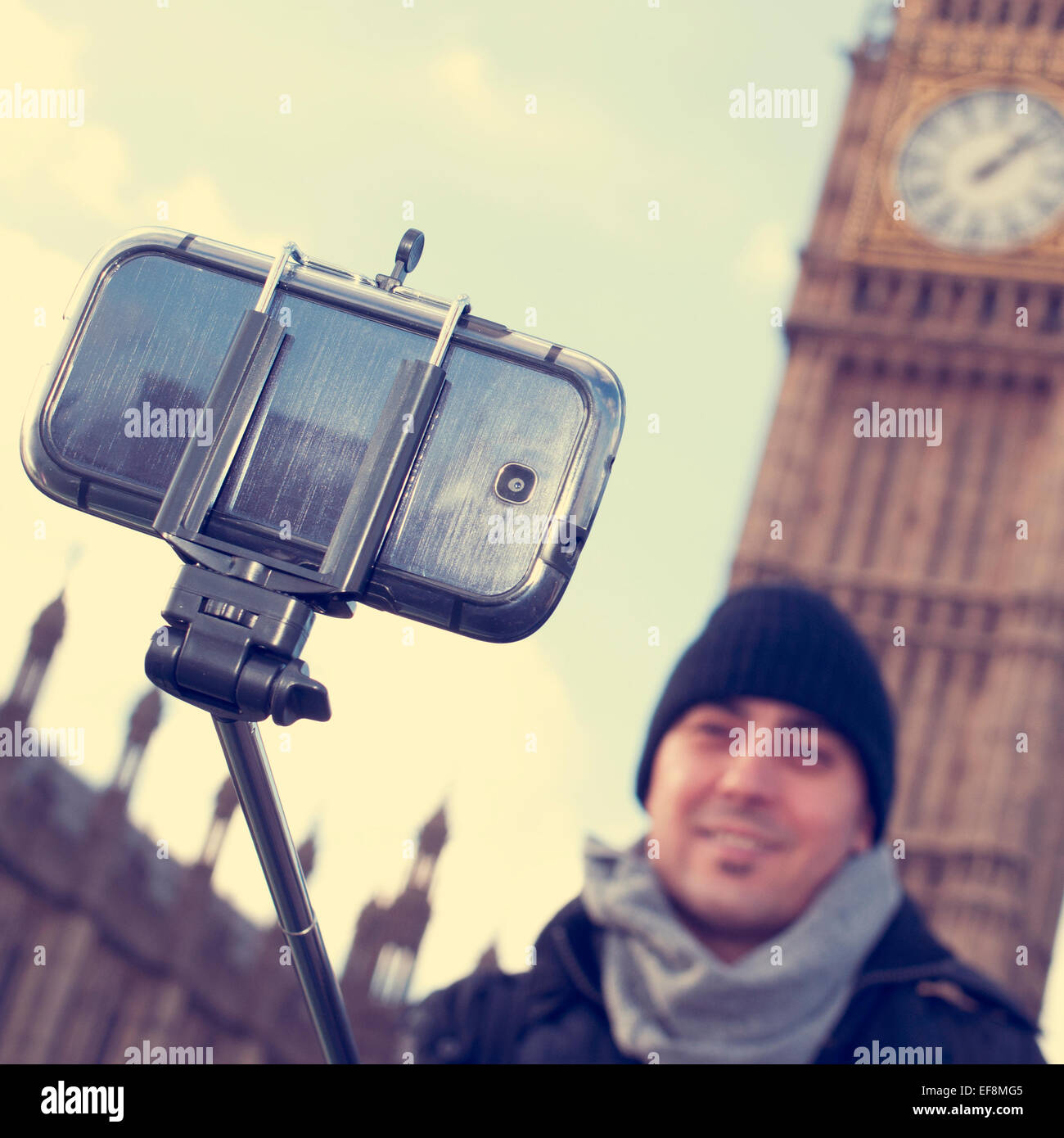 man taking a self-portrait with a selfie stick in front of the Big Ben in London, United Kingdom, with a filter - Stock Image