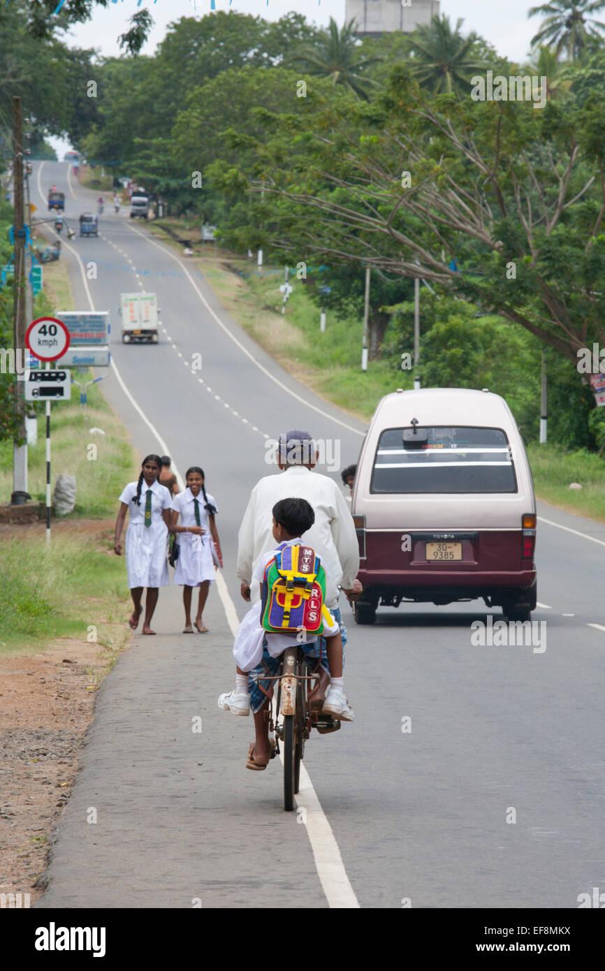 ROAD SCENE WITH TRAFFIC, BIKES AND SCHOOL CHILDREN - Stock Image