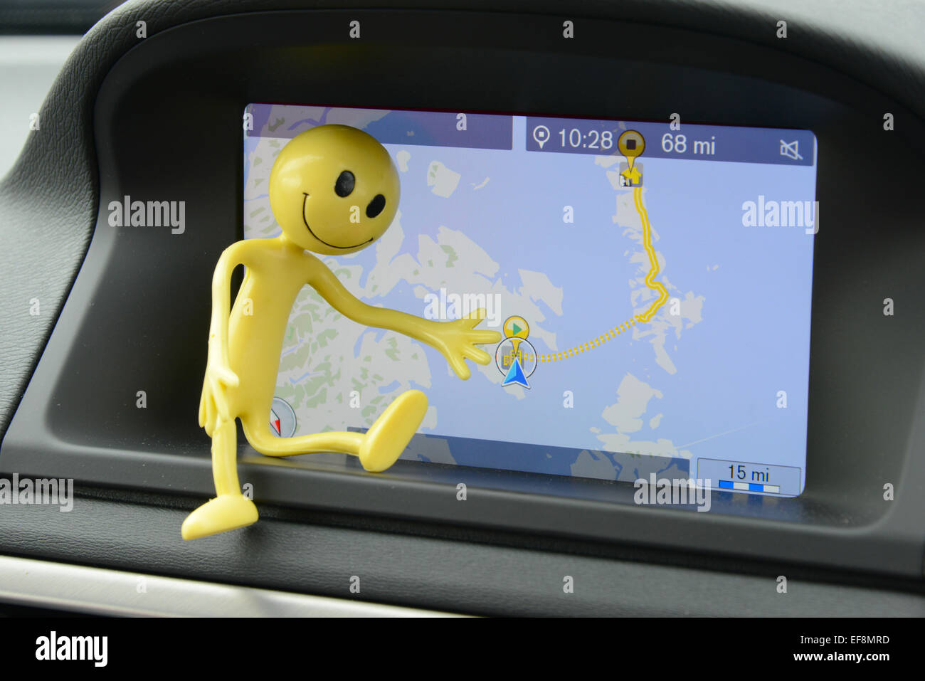 Yellow Smiley Man on holiday in the Outer Hebrides - pointing where he is on the satnav about to take the ferry - Stock Image