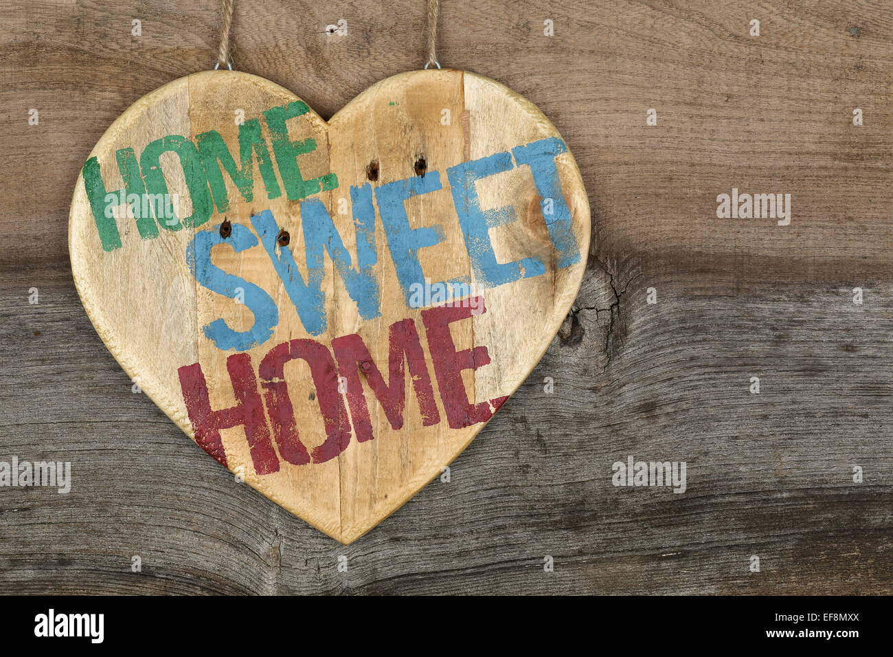 'Home Sweet Home' message wooden heart sign from recycled old palette on rough grey wooden background, copy - Stock Image