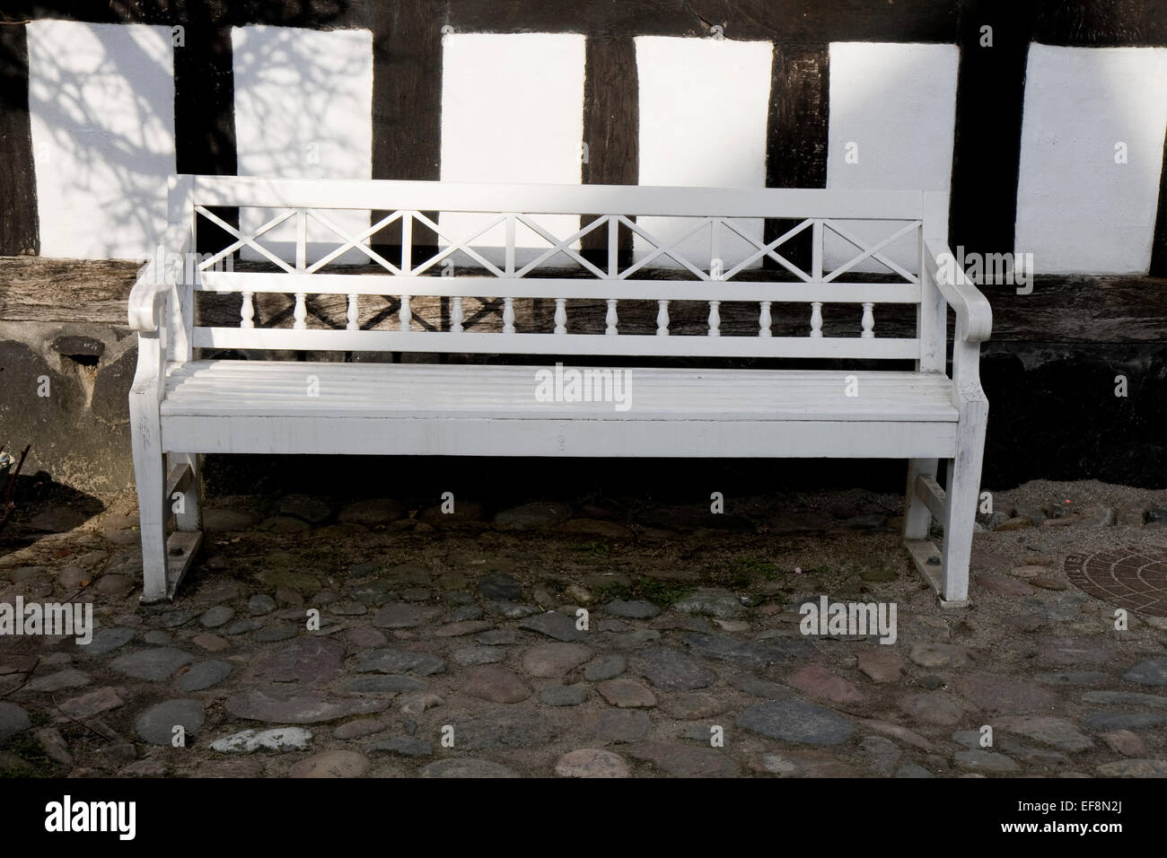 White bench in the shadow of a Half-timbered house - Stock Image