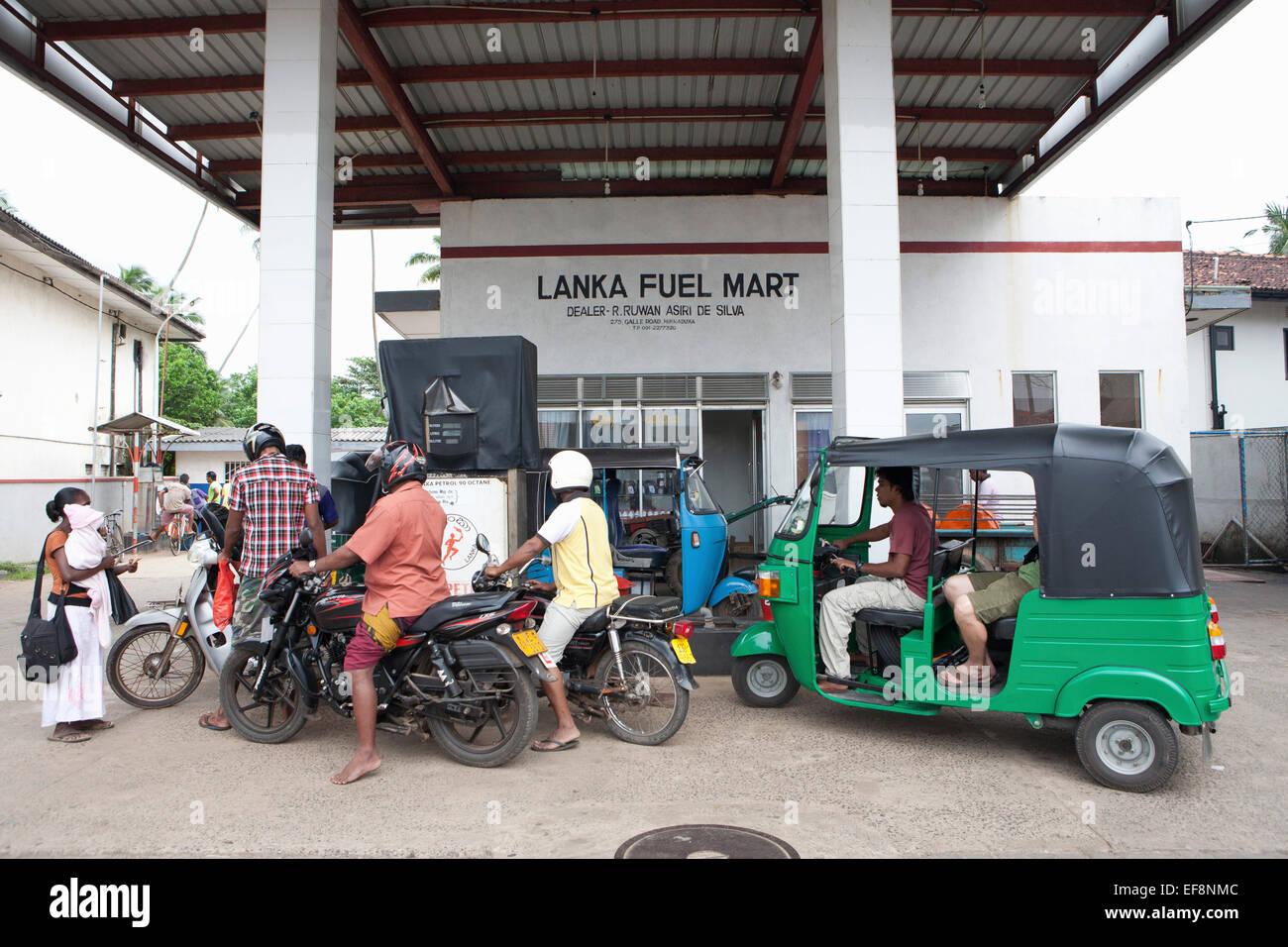 BIKES AND TUK TUK WAIT TO REFUEL AND LANKA FUEL MART - Stock Image