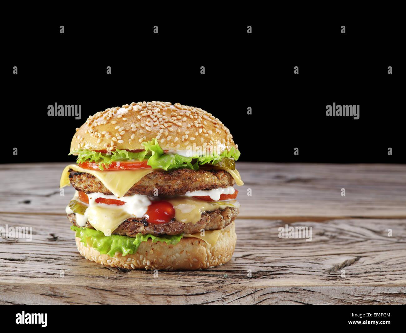 Hamburger on old wooden table. - Stock Image
