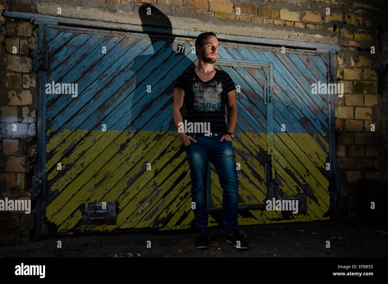Ukraine, Kiev, Young man standing in front of garage with Ukrainian flag painted on door - Stock Image