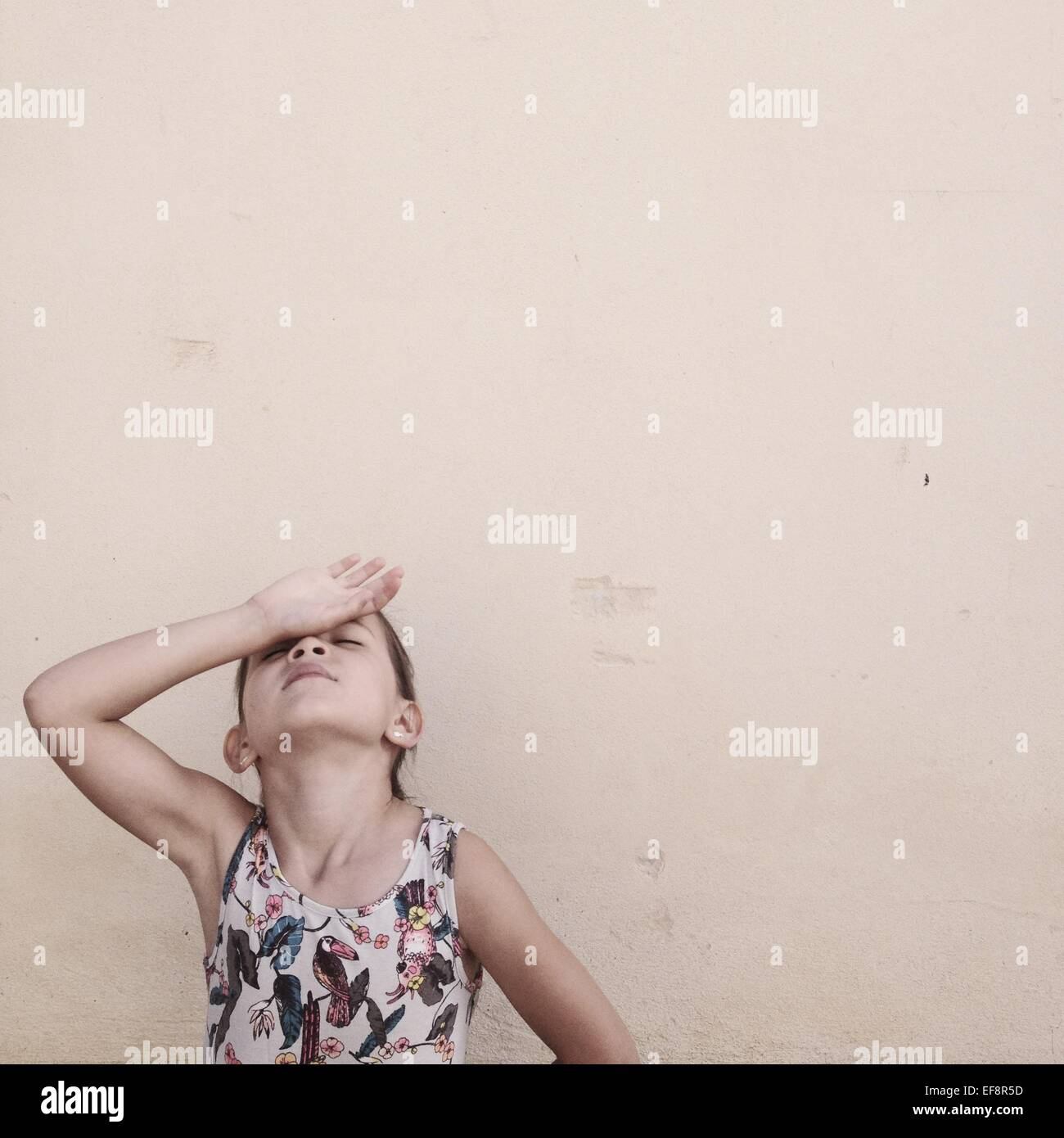 Portrait of girl with hand on forehead against beige wall - Stock Image