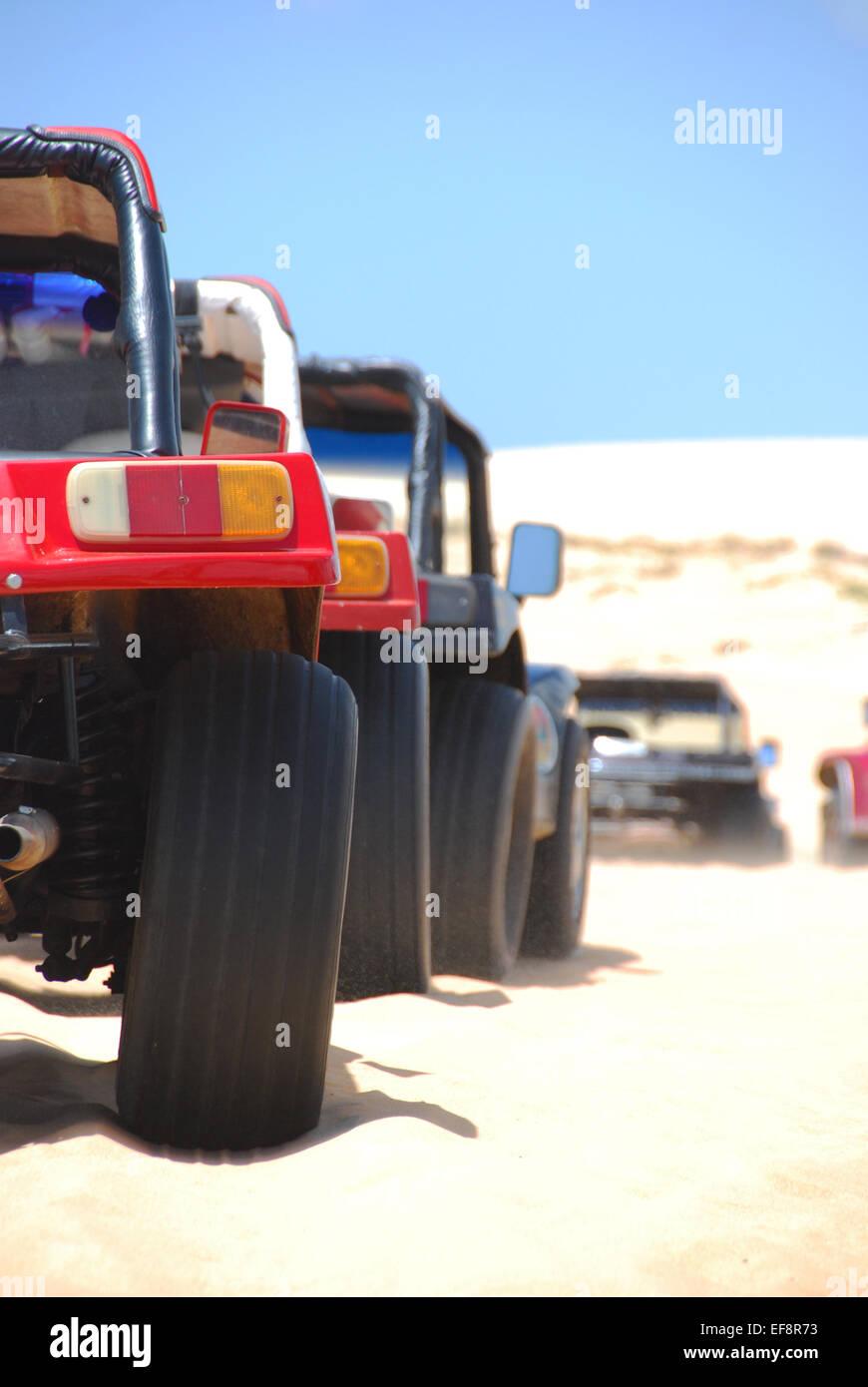 Brazil, Northeast Region, Ceara, Jijoca de Jericoacoara, Beach buggies parked in row on sand - Stock Image