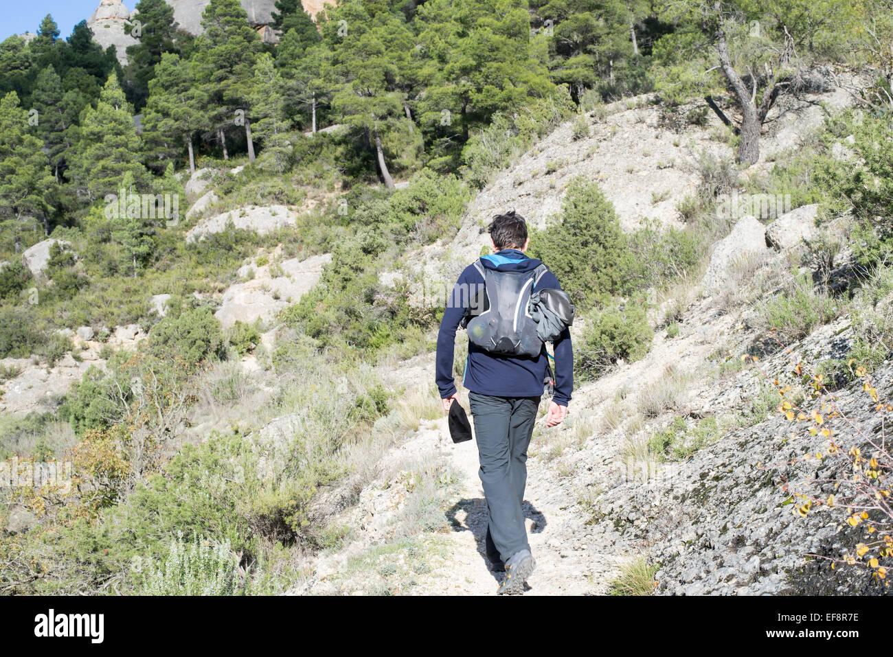 Spain, Catalonia, Tarragona, Montsant, Serra de Montsant, Ulldemolins, Hiker walking away along mountain trail - Stock Image