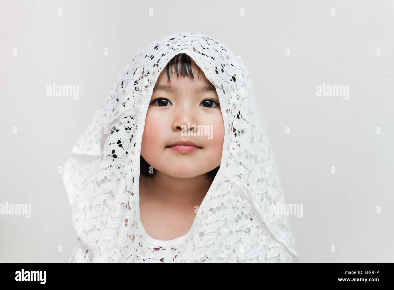 Australia, Melbourne, Portrait of young girl in lace hood - Stock Image