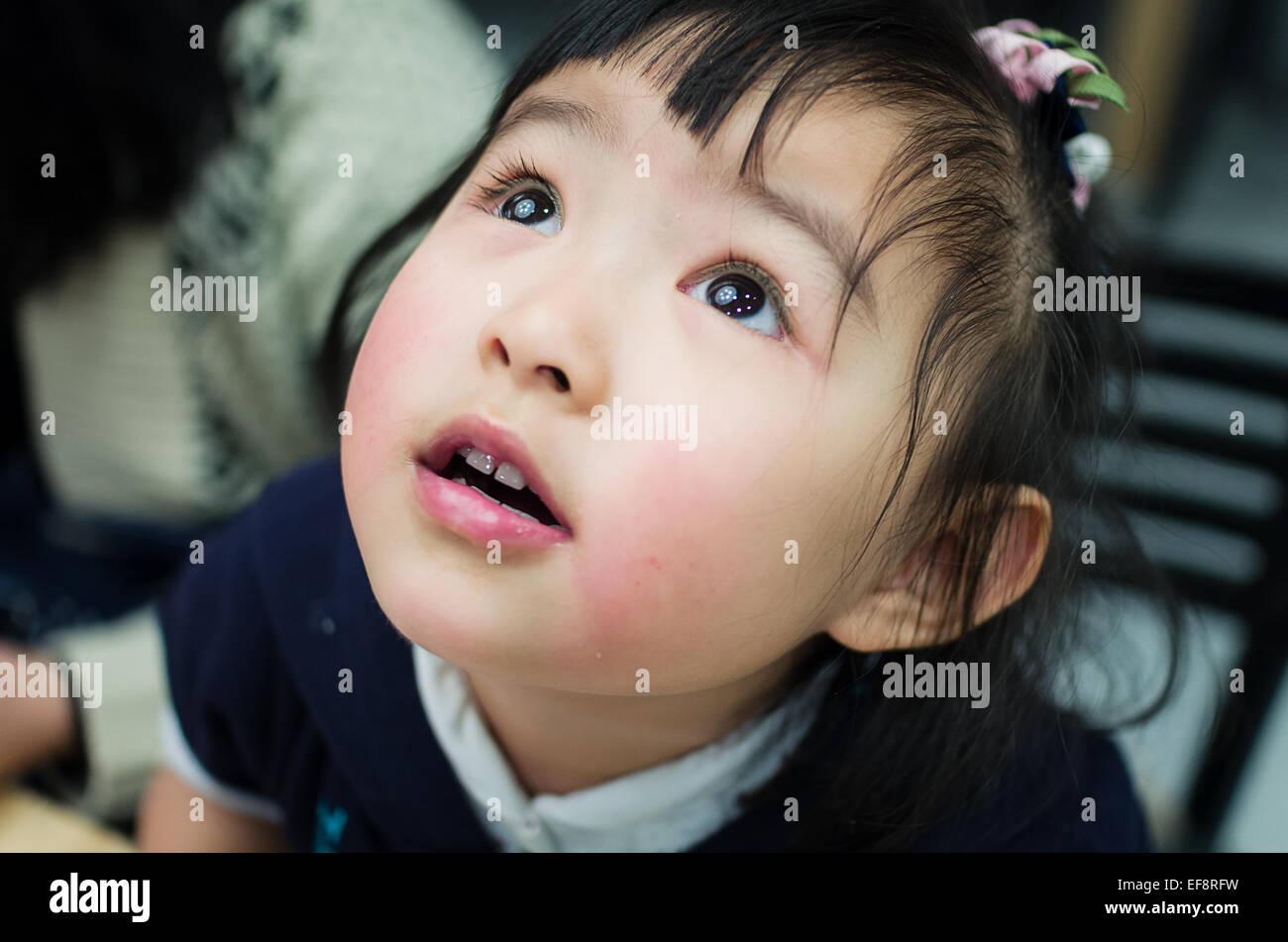 Australia, Melbourne, Headshot of young girl looking up - Stock Image
