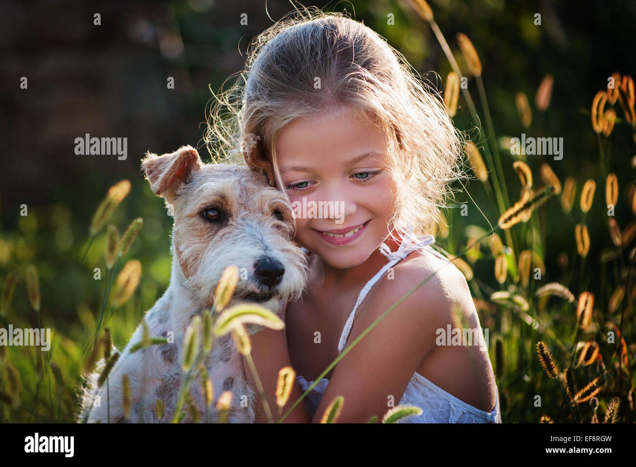 Portrait of girl (6-7) embracing dog - Stock Image