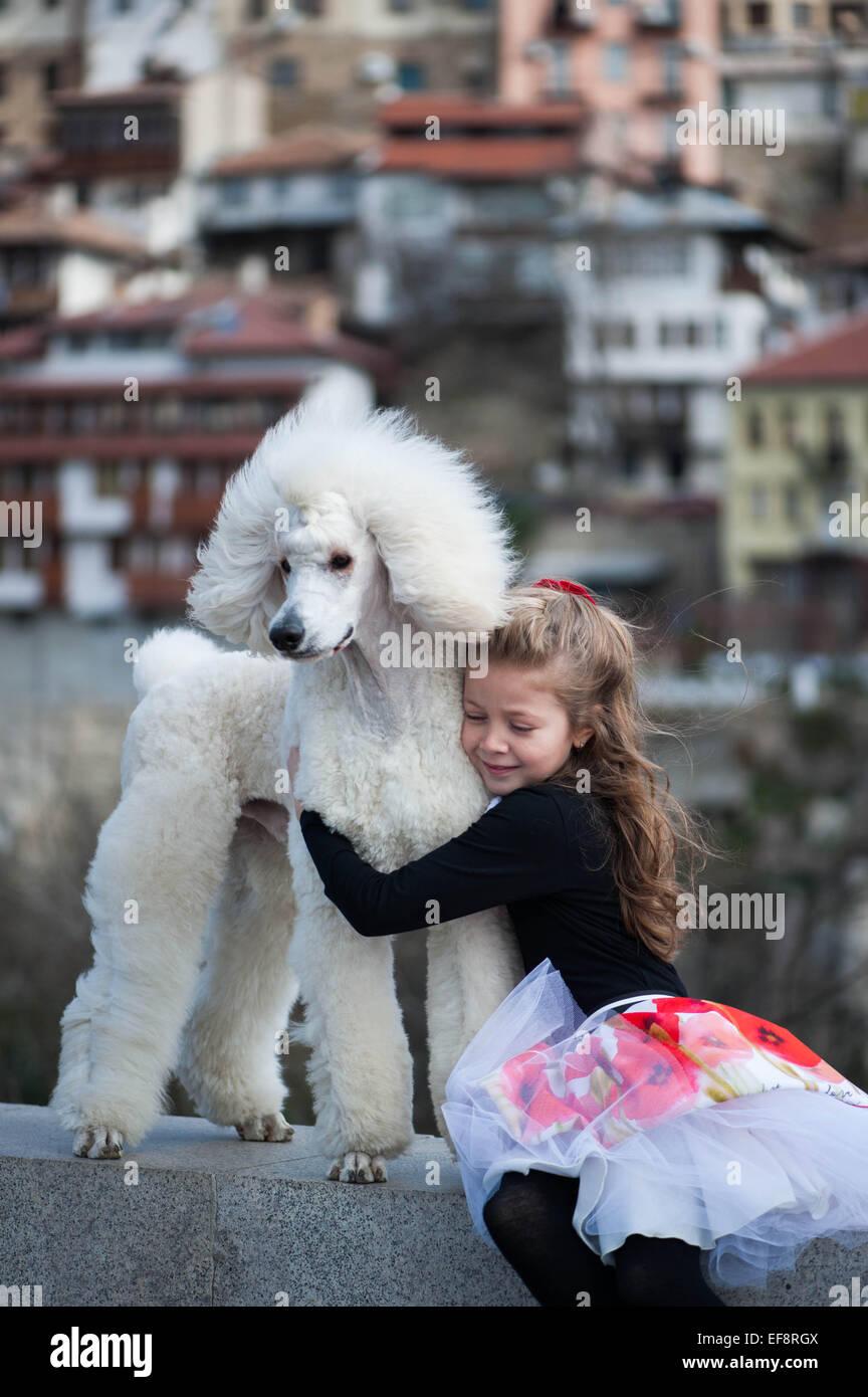 Portrait of girl (6-7) embracing large white poodle - Stock Image