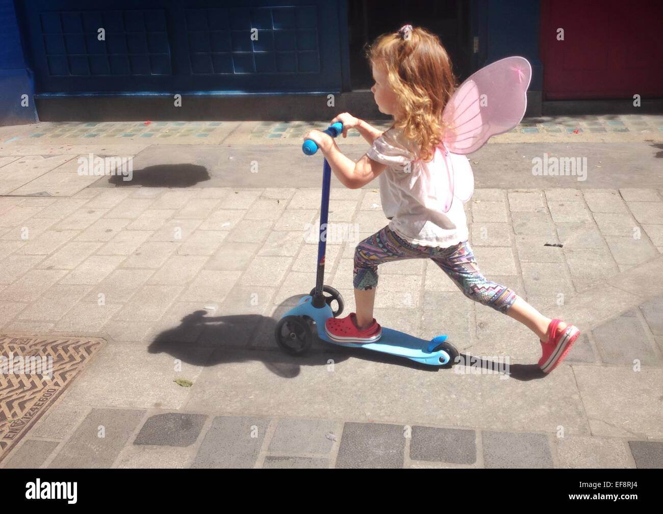 UK, England, London, Portrait of girl (2-3) with fairy wings riding scooter on city pavement Stock Photo