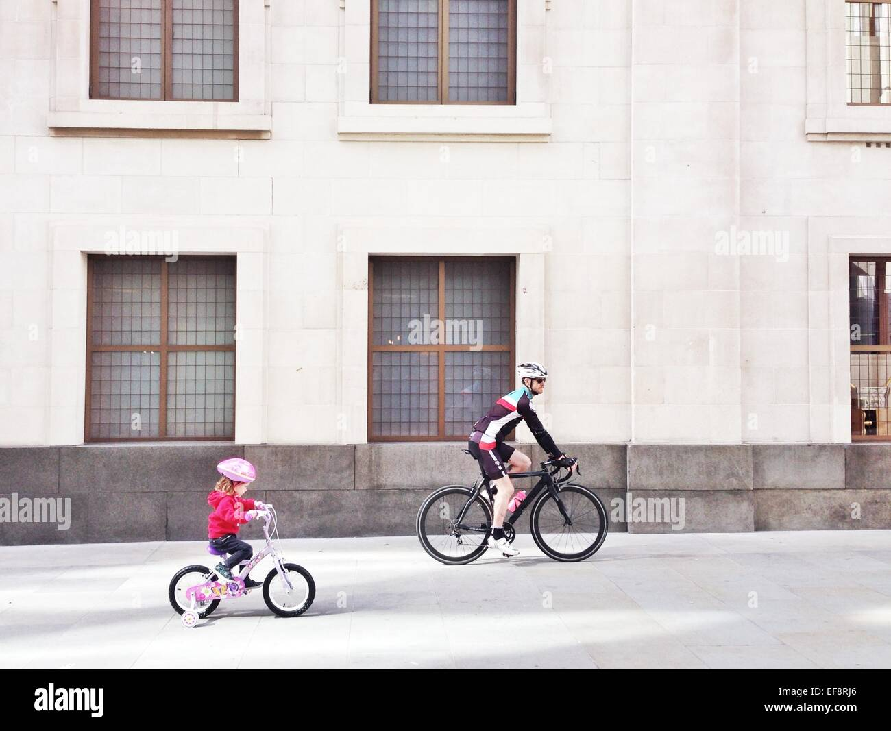 UK, England, London, Father and daughter cycling past building - Stock Image