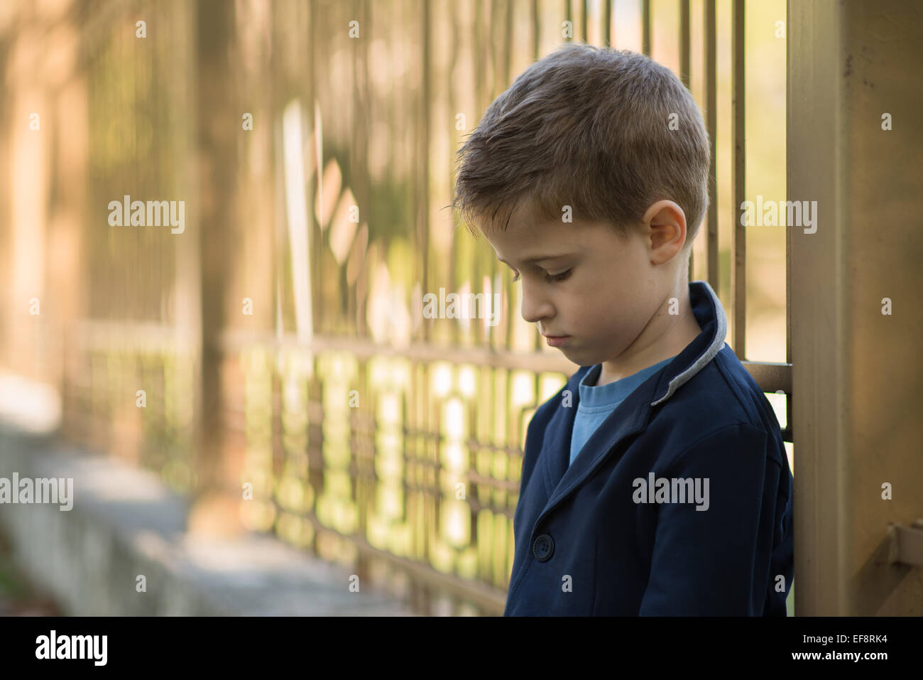 Portrait of a sad boy leaning against metal railings - Stock Image