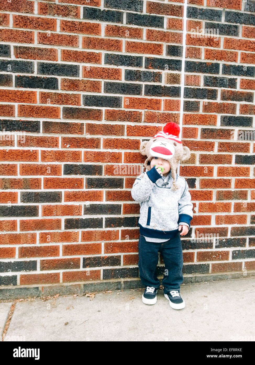 Boy leaning against brick wall - Stock Image