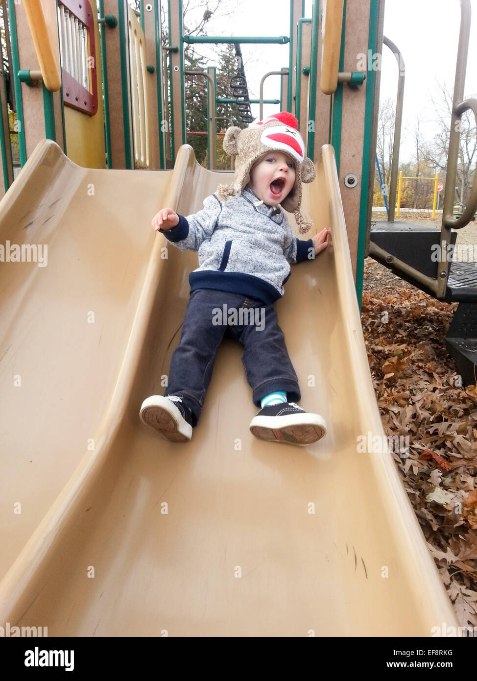 Boy sliding on playground - Stock Image
