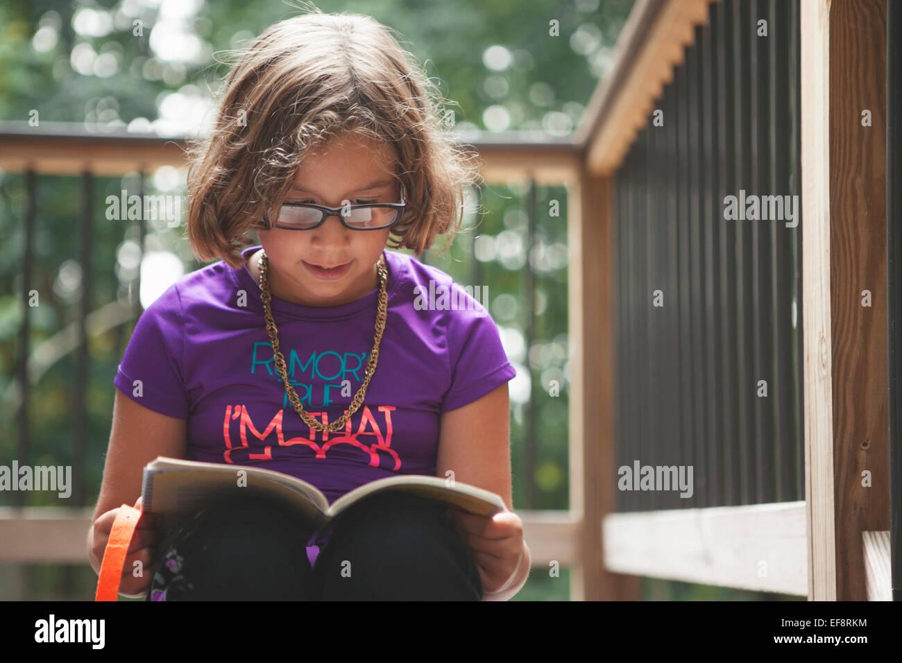 Girl (6-7) reading book on balcony - Stock Image