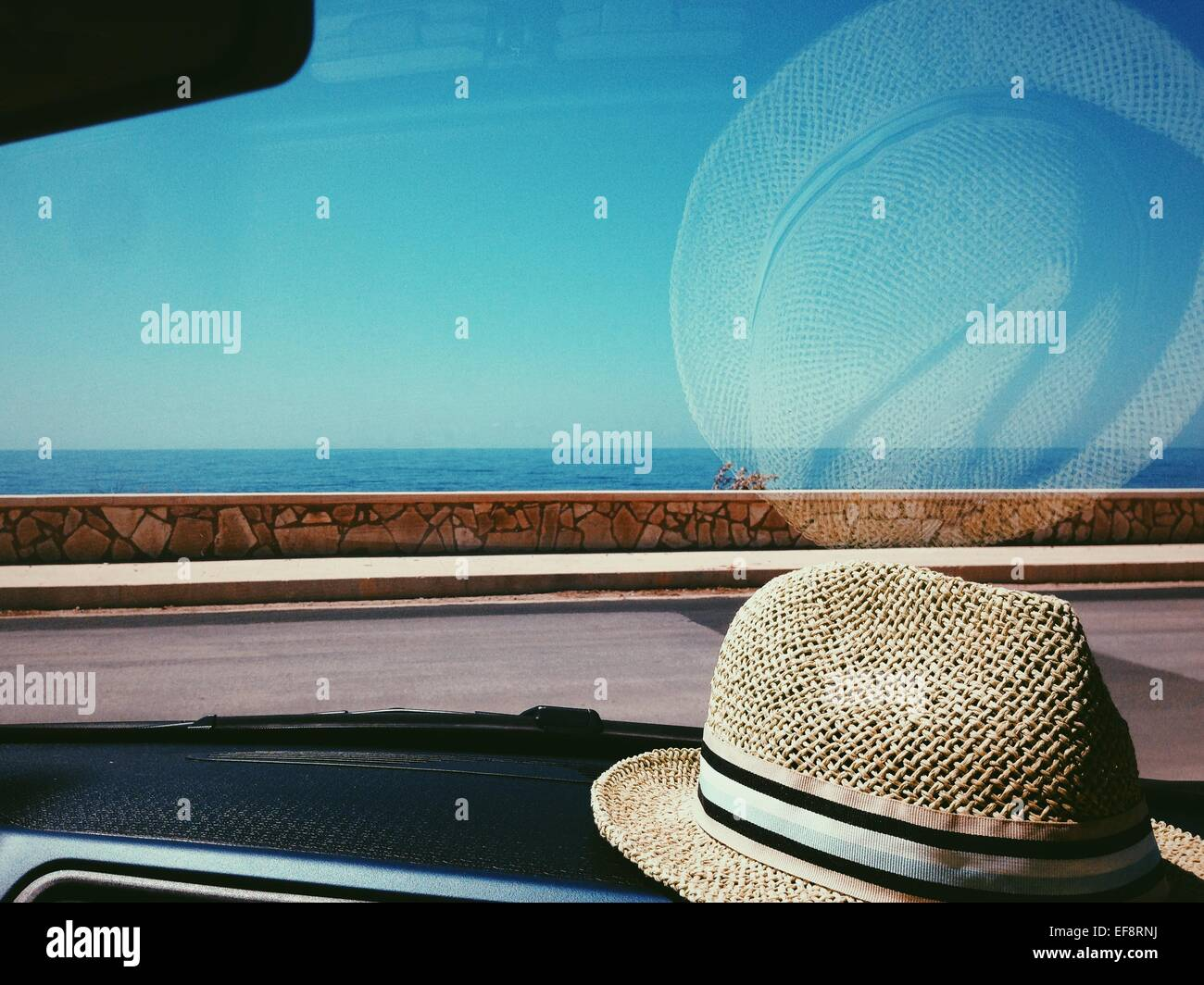 Straw hat on dashboard of car - Stock Image