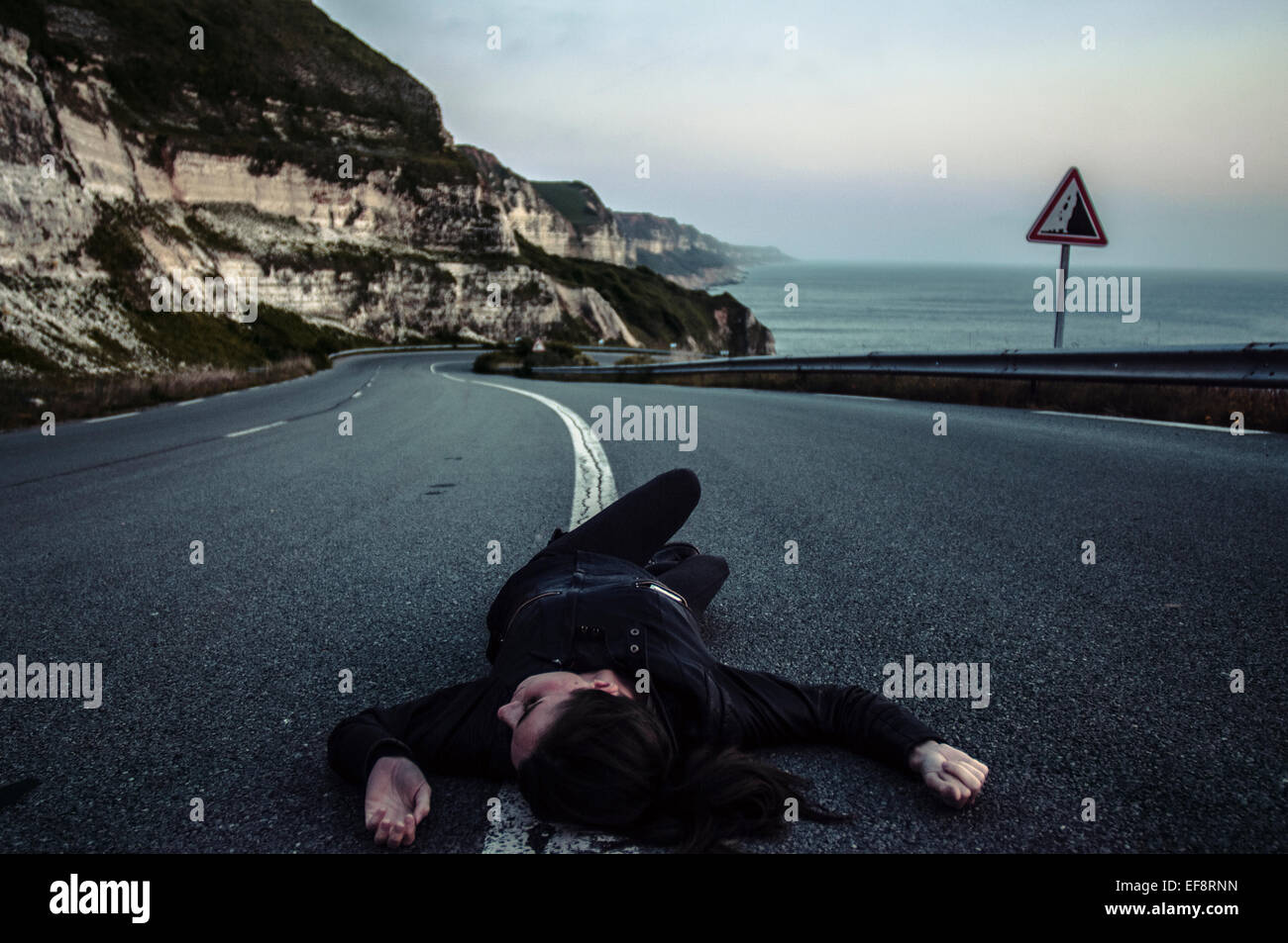 Woman lying down in middle of road - Stock Image