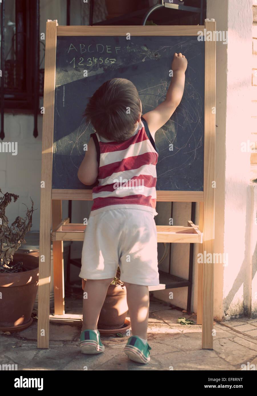 Boy writing on blackboard - Stock Image