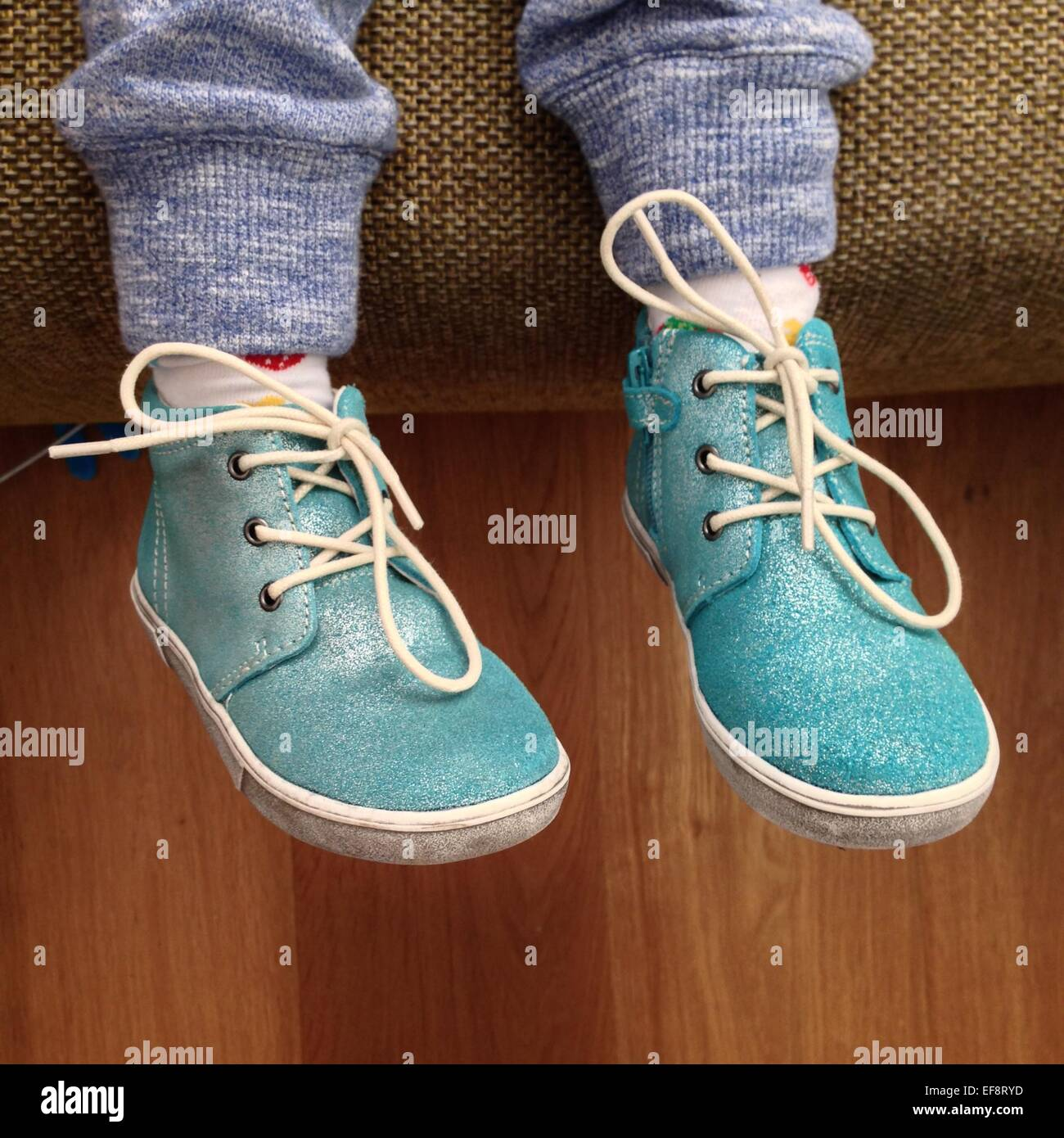 Cropped shot of legs of child wearing turquoise shoes - Stock Image