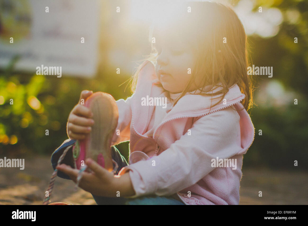 Portrait of girl (2-3) taking off shoe - Stock Image