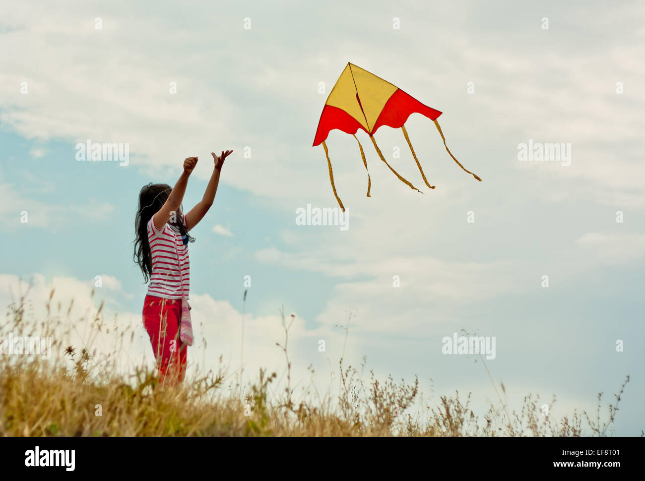 Portrait of girl (8-9) flying kite on hill - Stock Image