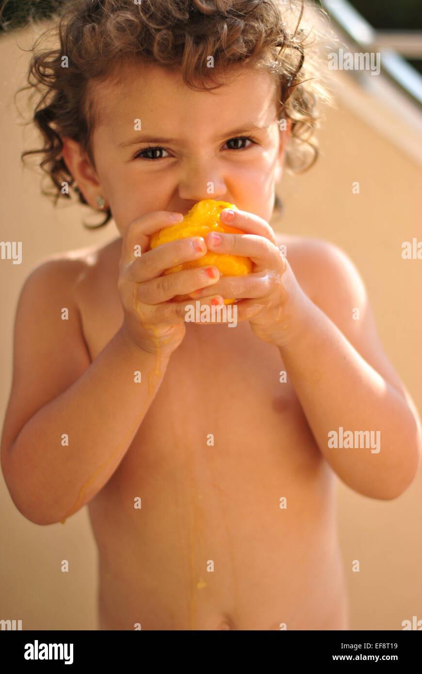Portrait of girl (2-3) eating peach - Stock Image