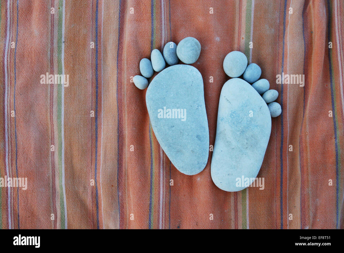 Stones laid out in shape of feet Stock Photo