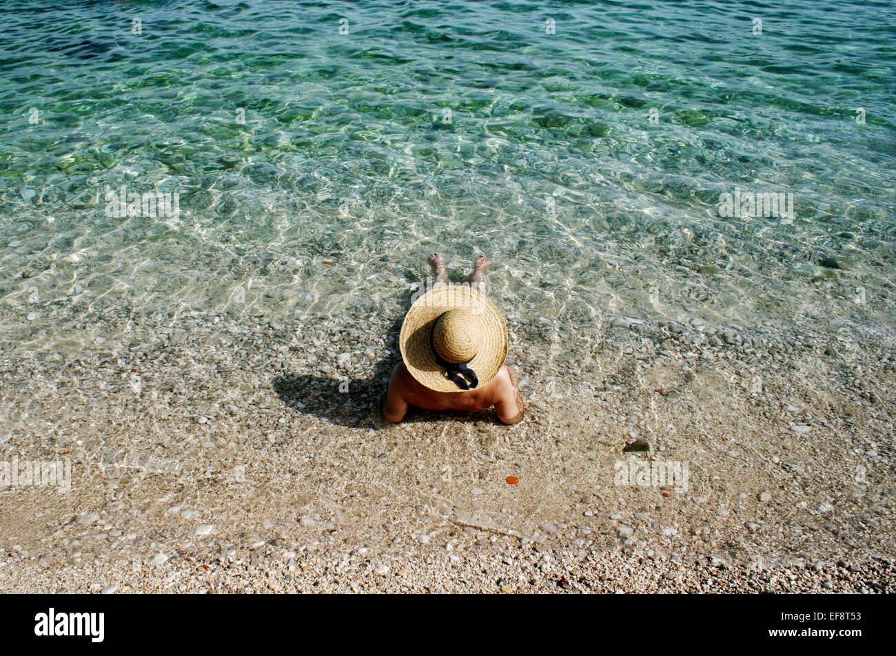 Croatia, Woman with straw hat sunbathing - Stock Image