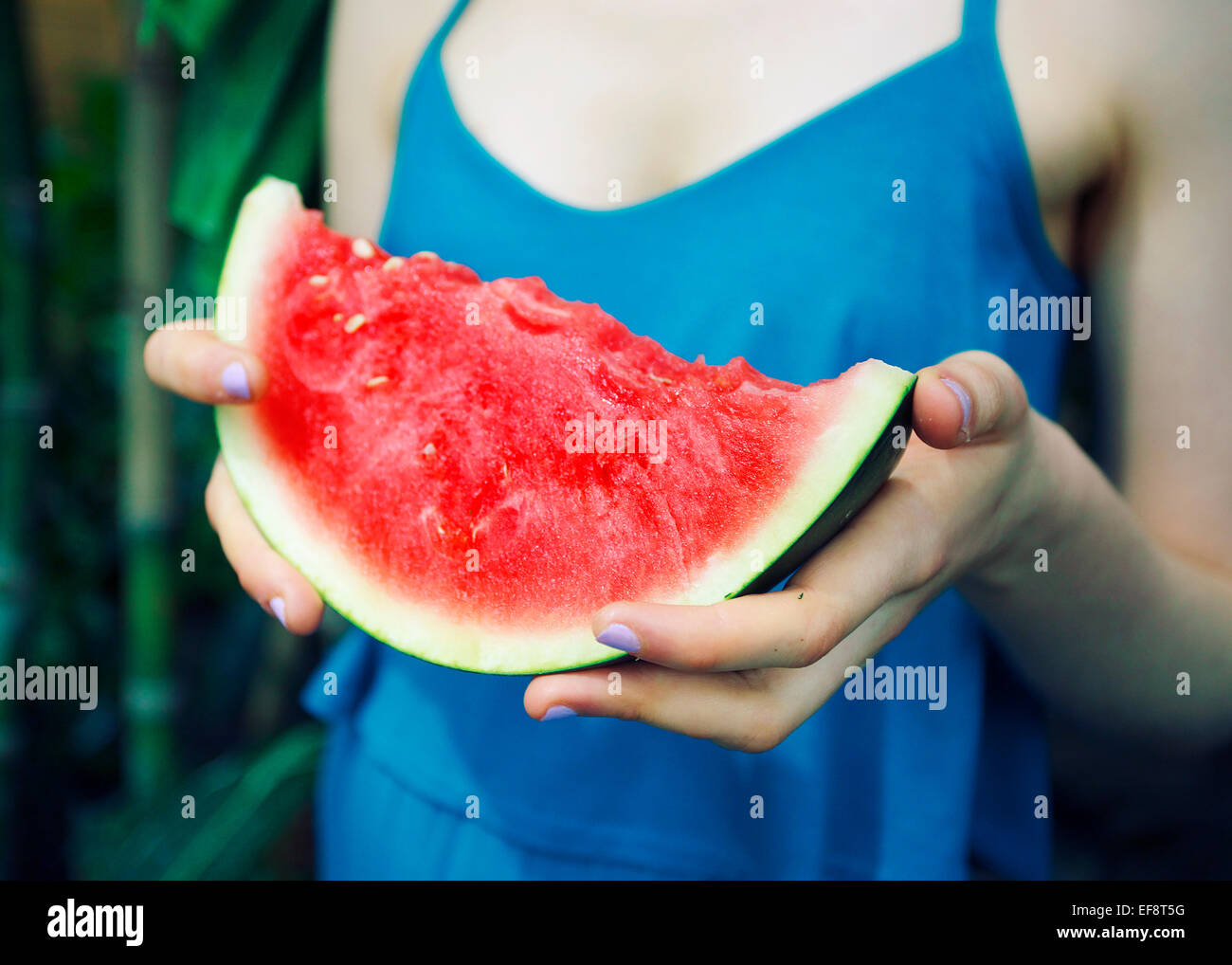 Woman holding slice of watermelon - Stock Image