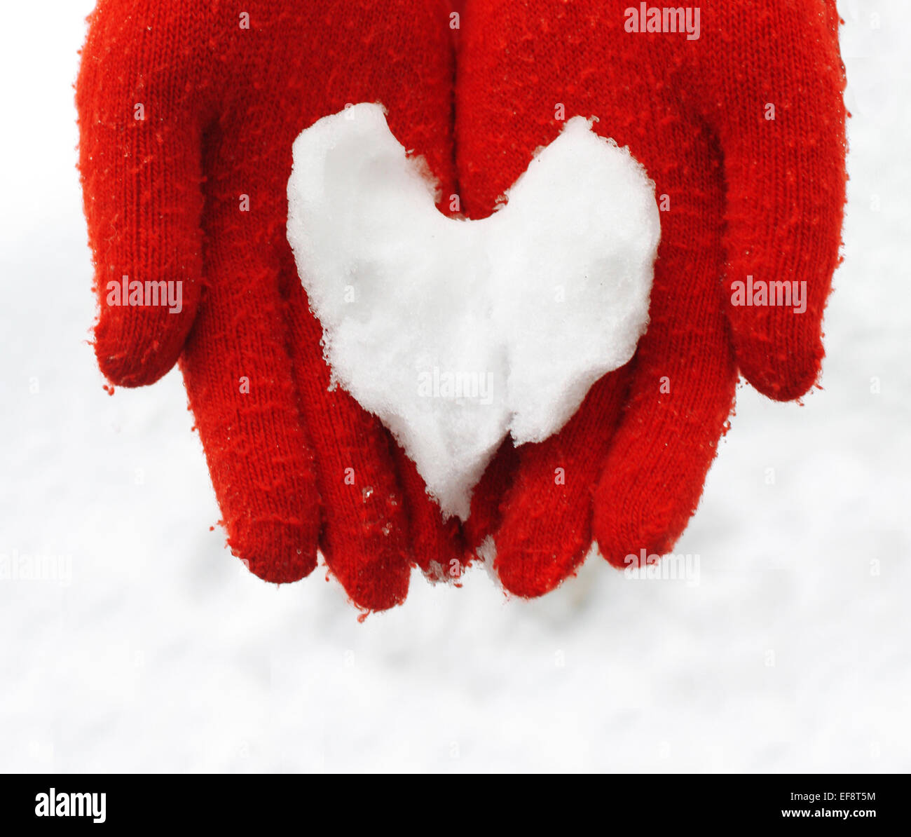 Finland, Close up of woman holding heart made of snow - Stock Image