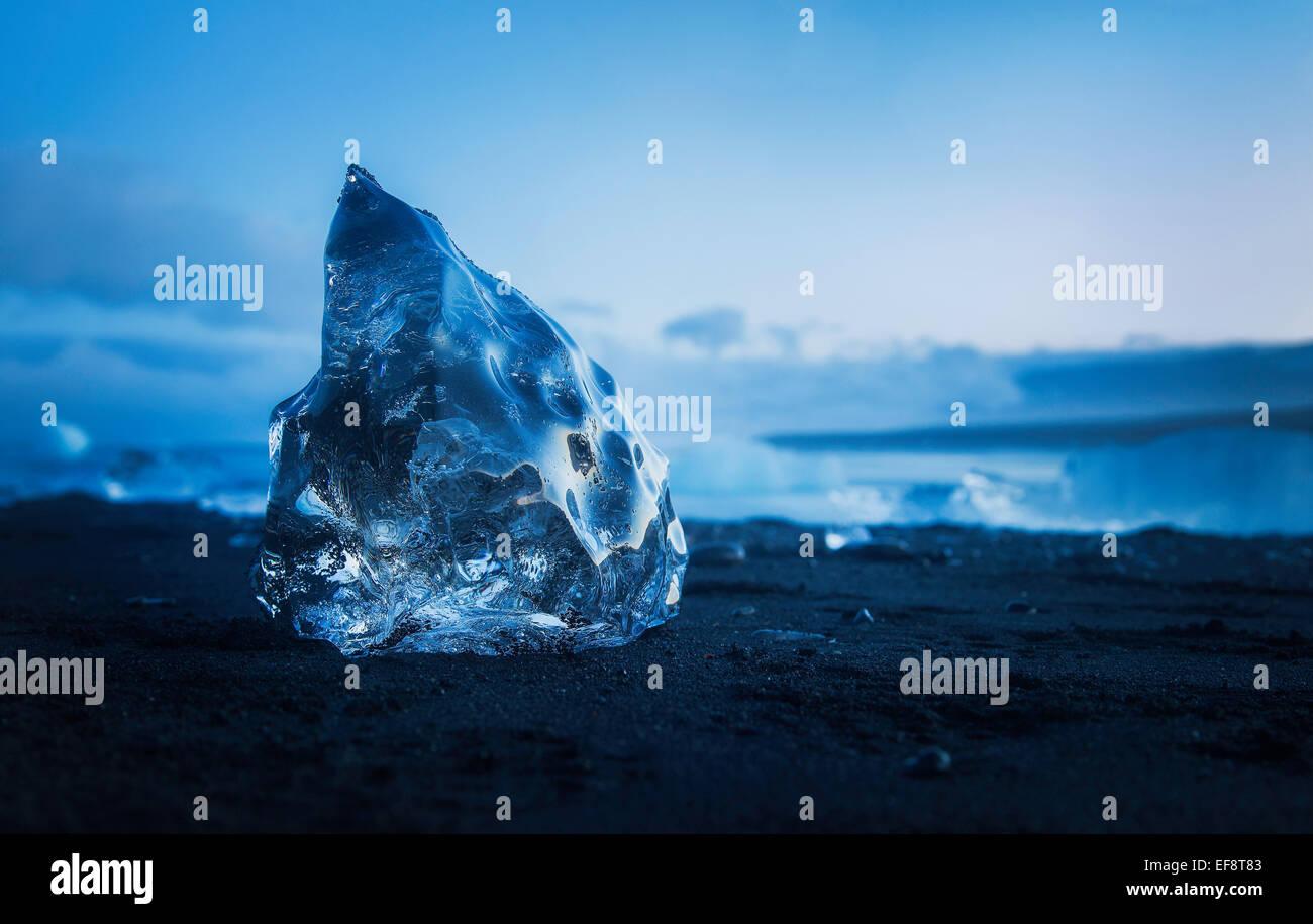Iceland, Ice cube melting on black sandy beach - Stock Image