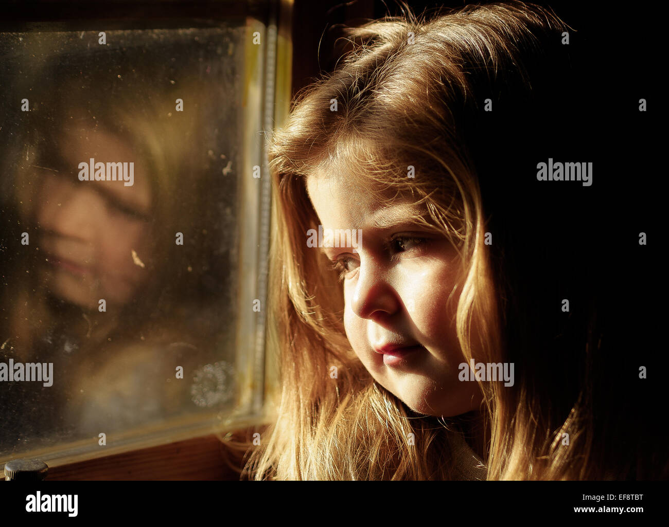 Portrait of girl sitting in train - Stock Image
