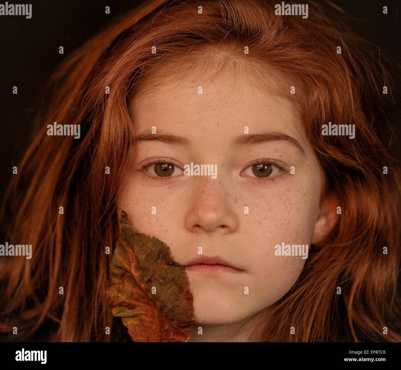 Portrait of girl with autumn leaf - Stock Image