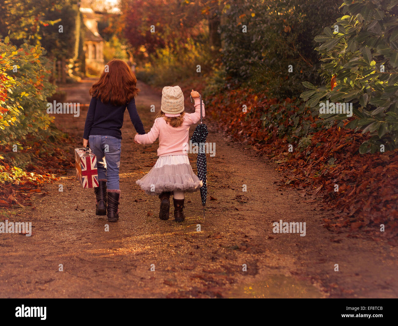 Two sisters walking country path holding union jack case and umbrella - Stock Image
