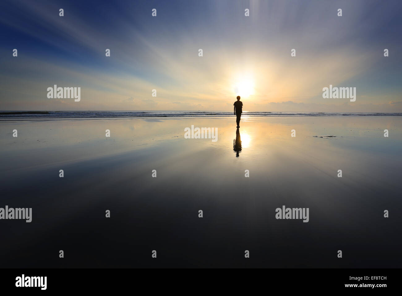 Boy walking on beach at sunset - Stock Image