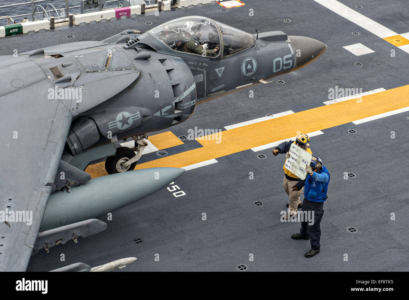 A US Sailor directs a US Marine Corps AV-8B Harrier II fighter aircraft to prepare for take off from the flight Stock Photo
