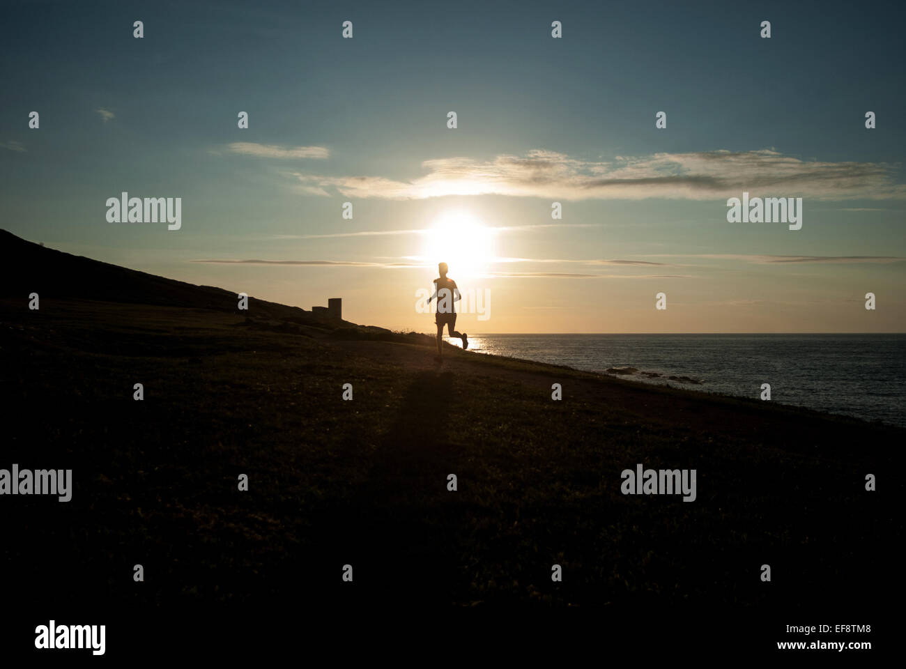 Silhouette of man running on beach at sunset, Galicia, Spain - Stock Image