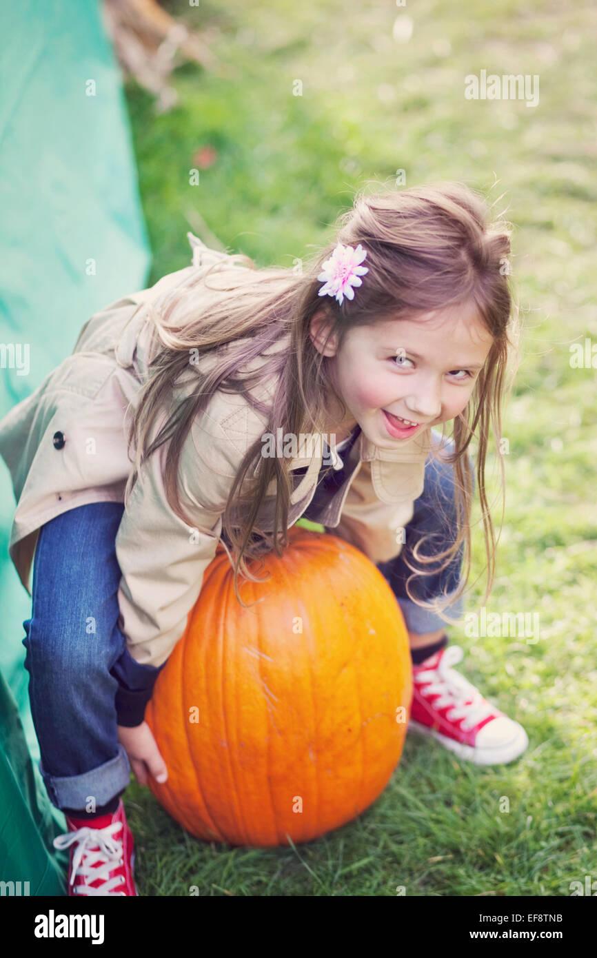 Girl (4-5) trying to lift big pumpkin - Stock Image
