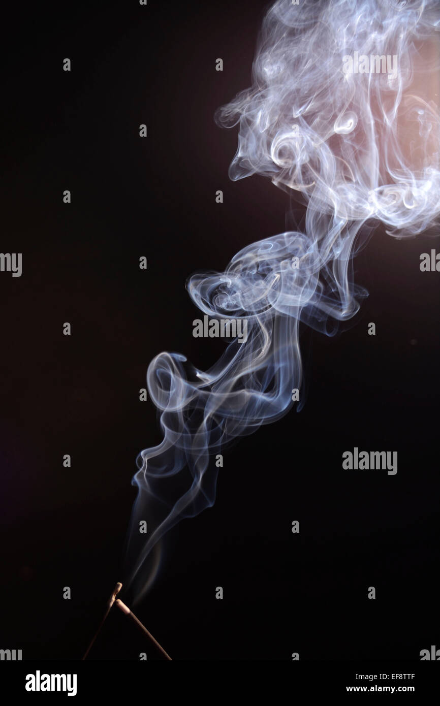 Curling smoke from two incense sticks - Stock Image